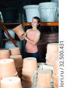 Купить «Young woman customer looking decorative clay pot for garden», фото № 32500431, снято 9 декабря 2019 г. (c) Яков Филимонов / Фотобанк Лори