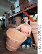 Купить «Young woman customer choosing big clay pot for garden», фото № 32500435, снято 9 декабря 2019 г. (c) Яков Филимонов / Фотобанк Лори