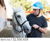Купить «Male farmer in helmet standing with white horse at stable outdoor», фото № 32500659, снято 6 декабря 2019 г. (c) Яков Филимонов / Фотобанк Лори