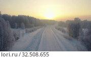 Купить «Aerial video view from low-altitude flying drone of a Sunrise over snowy winter road. Siberia, Russia», видеоролик № 32508655, снято 5 ноября 2019 г. (c) Serg Zastavkin / Фотобанк Лори
