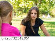 Купить «Девушка на пикнике внимательно слушает собеседника», фото № 32518951, снято 15 сентября 2019 г. (c) Иванов Алексей / Фотобанк Лори
