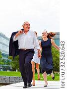 Zwei Geschäftsfrauen fangen laufenden Senior Manager im Freien. Стоковое фото, фотограф Zoonar.com/Robert Kneschke / age Fotostock / Фотобанк Лори