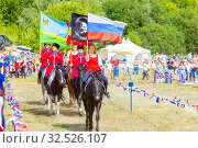 Купить «Russia, Samara, July 2019: Solemn entry of a group of horse racing with flags in the meadow of the festival.», фото № 32526107, снято 28 июля 2019 г. (c) Акиньшин Владимир / Фотобанк Лори