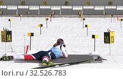 Sportswoman biathlete aiming, rifle shooting prone position. Kamchatka biathlete Babkina Maria in shooting range. Junior biathlon competitions East of Cup (2019 год). Редакционное видео, видеограф А. А. Пирагис / Фотобанк Лори