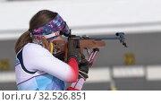 Sportswoman biathlete aiming, rifle shooting standing position. Kamchatka biathlete Babkina Maria in shooting range. Junior biathlon competitions East of Cup (2019 год). Редакционное видео, видеограф А. А. Пирагис / Фотобанк Лори