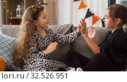 Купить «girls in halloween costumes playing game at home», видеоролик № 32526951, снято 14 ноября 2019 г. (c) Syda Productions / Фотобанк Лори