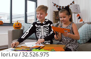 Купить «kids in halloween costumes doing crafts at home», видеоролик № 32526975, снято 14 ноября 2019 г. (c) Syda Productions / Фотобанк Лори