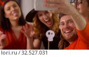 Купить «happy friends in halloween costumes taking selfie», видеоролик № 32527031, снято 18 ноября 2019 г. (c) Syda Productions / Фотобанк Лори