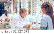 Купить «Smiling elderly woman optician offering stylish glasses in modern optical store», видеоролик № 32527375, снято 20 февраля 2020 г. (c) Яков Филимонов / Фотобанк Лори