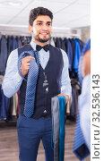 Guy is picking up tie for waistcoat in front of the mirror. Стоковое фото, фотограф Яков Филимонов / Фотобанк Лори