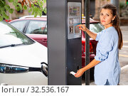 Купить «Young woman paying for parking in modern parking meter on city street», фото № 32536167, снято 16 февраля 2020 г. (c) Яков Филимонов / Фотобанк Лори