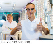 Male client standing with new spectacles and thumb up. Стоковое фото, фотограф Яков Филимонов / Фотобанк Лори