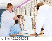 Купить «Two optometrists testing eyesight of woman», фото № 32536351, снято 27 августа 2019 г. (c) Яков Филимонов / Фотобанк Лори