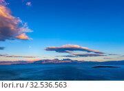 Cretan seascape at sunset with mountains, moon and clouds. Crete, Greece. (2019 год). Стоковое фото, фотограф photoff / Фотобанк Лори