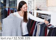 Купить «Portrait of smiling woman choosing sweater», фото № 32538335, снято 17 января 2018 г. (c) Яков Филимонов / Фотобанк Лори