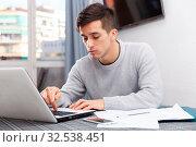 Купить «Upset young man counts family budget on laptop», фото № 32538451, снято 27 февраля 2020 г. (c) Яков Филимонов / Фотобанк Лори