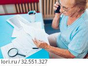 Elderly woman at home contacting custumer services after recieving a bill. Стоковое фото, фотограф Zoonar.com/Tomas Anderson / easy Fotostock / Фотобанк Лори