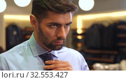 Man tying a tie at wear clothing store. Стоковое видео, видеограф Илья Шаматура / Фотобанк Лори