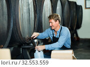 man pouring wine from wood in cellar. Стоковое фото, фотограф Яков Филимонов / Фотобанк Лори
