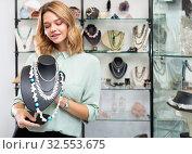 Купить «Girl showing pearl necklace on stand», фото № 32553675, снято 3 декабря 2019 г. (c) Яков Филимонов / Фотобанк Лори