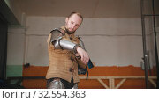 Купить «A man putting on a knight armour - putting on full armor for the training», видеоролик № 32554363, снято 30 мая 2020 г. (c) Константин Шишкин / Фотобанк Лори