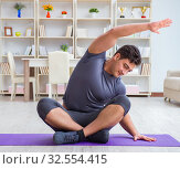 Купить «Young man exercising at home in sports and healthy lifestyle con», фото № 32554415, снято 3 мая 2017 г. (c) Elnur / Фотобанк Лори