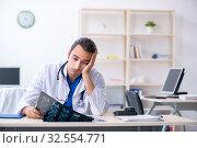 Купить «Young male doctor working in the clinic», фото № 32554771, снято 21 июня 2019 г. (c) Elnur / Фотобанк Лори