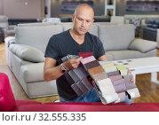 Купить «Client choosing upholstery fabric from catalog with samples», фото № 32555335, снято 29 октября 2018 г. (c) Яков Филимонов / Фотобанк Лори