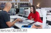 Купить «Consultant helping woman choosing upholstery fabric», фото № 32555351, снято 29 октября 2018 г. (c) Яков Филимонов / Фотобанк Лори