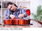 Купить «Young handsome repairman repairing cello», фото № 32555835, снято 4 апреля 2019 г. (c) Elnur / Фотобанк Лори