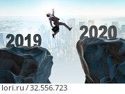 Купить «Businessman jumping from year 2019 to 2020», фото № 32556723, снято 24 мая 2020 г. (c) Elnur / Фотобанк Лори