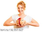 Купить «Junge blonde Frau hält Sparschwein als Finanzierung Konzept in ihren Händen», фото № 32557027, снято 26 мая 2020 г. (c) age Fotostock / Фотобанк Лори
