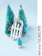 Купить «Christmas winter composition. Wooden white sledge and fir trees on blue», фото № 32562975, снято 26 ноября 2019 г. (c) Papoyan Irina / Фотобанк Лори