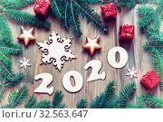 Купить «New Year 2020 background with 2020 figures, Christmas toys, green fir tree branches on the wooden background», фото № 32563647, снято 29 ноября 2016 г. (c) Зезелина Марина / Фотобанк Лори
