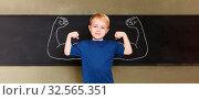 Selbstbewusstes Kind steht mit Muskeln vor der Tafel in einer Grundschule. Стоковое фото, фотограф Zoonar.com/Robert Kneschke / age Fotostock / Фотобанк Лори