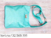 Handmade turquoise colour leather shoulder bag on gray wooden table. Стоковое фото, фотограф Zoonar.com/Valery Voennyy / easy Fotostock / Фотобанк Лори