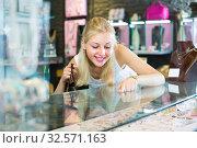 Купить «girl near glass showcase in bijouterie store», фото № 32571163, снято 10 декабря 2019 г. (c) Яков Филимонов / Фотобанк Лори