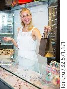 Купить «Glad female seller standing in bijouterie boutique», фото № 32571171, снято 10 декабря 2019 г. (c) Яков Филимонов / Фотобанк Лори