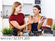 Купить «Two smiling young female friends looking cosmetics before make-up at table», фото № 32571203, снято 29 августа 2018 г. (c) Яков Филимонов / Фотобанк Лори