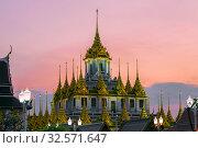 Вершина чеди Лоха Прасат буддистского храма Wat Ratchanatdaram  на фоне закатного неба. Бангкок, Таиланд (2018 год). Стоковое фото, фотограф Виктор Карасев / Фотобанк Лори