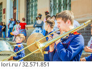 Купить «Russia, Samara, June 2017: a young man plays a trumpet for the participants of the procession, dedicated to school leavers on Leningradskaya Street on a sunny summer day.», фото № 32571851, снято 25 мая 2017 г. (c) Акиньшин Владимир / Фотобанк Лори