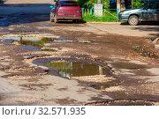 Купить «A puddle on a broken asphalt road.», фото № 32571935, снято 6 июня 2017 г. (c) Акиньшин Владимир / Фотобанк Лори