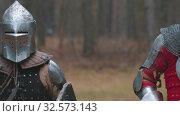 Купить «Two men knightes running in the row in the forest in full armour holding weapons», видеоролик № 32573143, снято 8 июля 2020 г. (c) Константин Шишкин / Фотобанк Лори