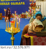 Купить «Russia, Samara, April 2017: a believing woman performs the worship of the ark with a part of the relics of St. Seraphim of Sarov. Burning candles in standing in a candlestick. Text in Russian: samara.», фото № 32576971, снято 21 апреля 2017 г. (c) Акиньшин Владимир / Фотобанк Лори