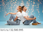 Купить «happy couple in white t-shirts sitting on floor», фото № 32580995, снято 6 октября 2019 г. (c) Syda Productions / Фотобанк Лори