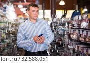 Купить «Buyer chooses the goods in the store», фото № 32588051, снято 22 октября 2019 г. (c) Яков Филимонов / Фотобанк Лори
