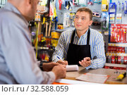 Adult salesman offering tools to man. Стоковое фото, фотограф Яков Филимонов / Фотобанк Лори
