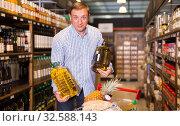Купить «Smiling male customer choosing olive oil», фото № 32588143, снято 9 октября 2019 г. (c) Яков Филимонов / Фотобанк Лори