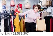 Купить «Woman choosing colorful blouse», фото № 32588307, снято 7 февраля 2017 г. (c) Яков Филимонов / Фотобанк Лори