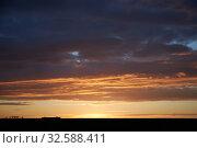 Купить «Orange rays of the sun at sunset illuminate dense clouds», фото № 32588411, снято 2 мая 2019 г. (c) Олег Белов / Фотобанк Лори
